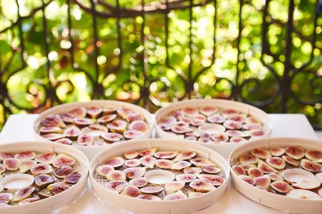 Процесс сушки нарезанного инжира на тарелках на столе на балконе