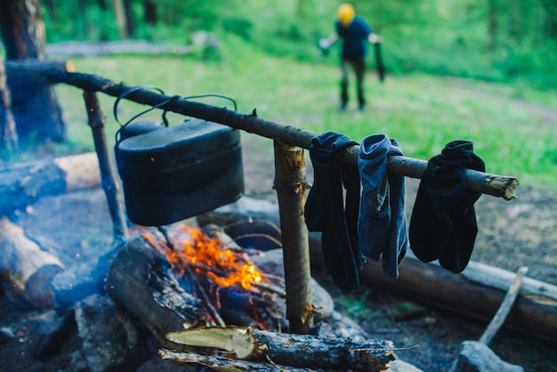 Drying wet clothing on the bonfire during camping. socks drying on fire. cauldron and kettle above campfire. cooking of food on nature. firewood and branches in fire. active rest in forest.