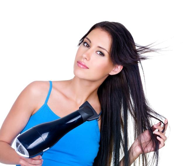 Asciugatura dei capelli castani lunghi della donna con asciugacapelli - isolato su sfondo bianco