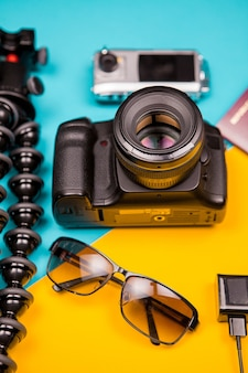 Dslr and action camera next to a tripod, sunglasses and passport on two colored background. pastel colors. travel concept