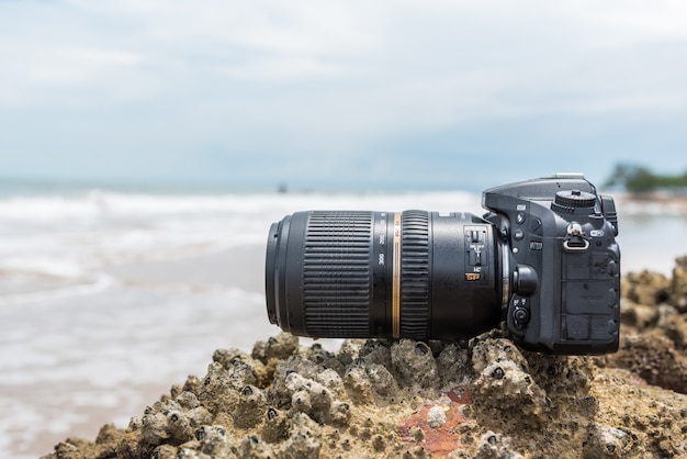 Dslr camera on beach wet from water sea wave