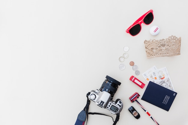 Dslr camera, passport, currencies, sunglasses and toys on bright backdrop