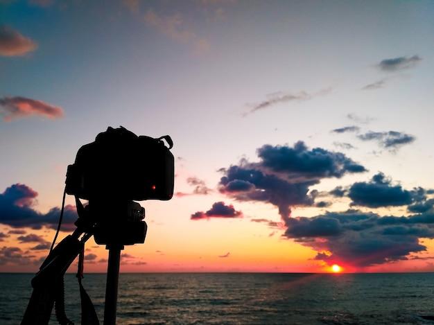 Камера dslr фотографируя холмы тосканы. съемка камеры dslr на закате городского пейзажа с отражением моря