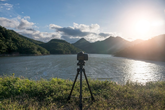 Dslr camera on a tripod with the sunrise with lake