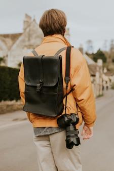 写真家の肩にぶら下がっているストラップ付きデジタル一眼レフカメラ