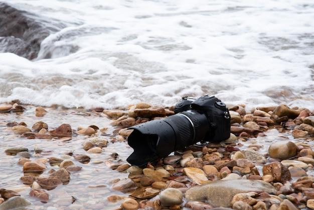 旅行の際に石のビーチで水海の波に濡れた望遠レンズ付きデジタル一眼レフカメラと写真家による防水デモを極限環境で使用してテスト