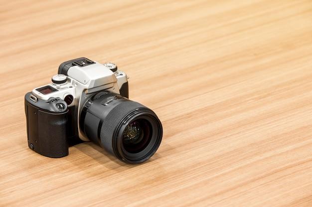 Dslr camera on wooden desk background.