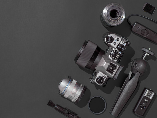 Рабочее место фотографа с камерой dslr, объектив, планшет и аксессуары камеры на черном фоне. камера, фотография, визуальное содержание концепции. плоская планировка или вид сверху. копировать пространство жесткий свет.