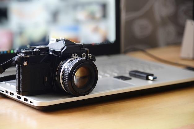 デジタルスタジオ写真ワークステーション。レトロフィルムdslrカメラ、ラップトップコンピューターの画面、フラッシュドライブのメモリカード
