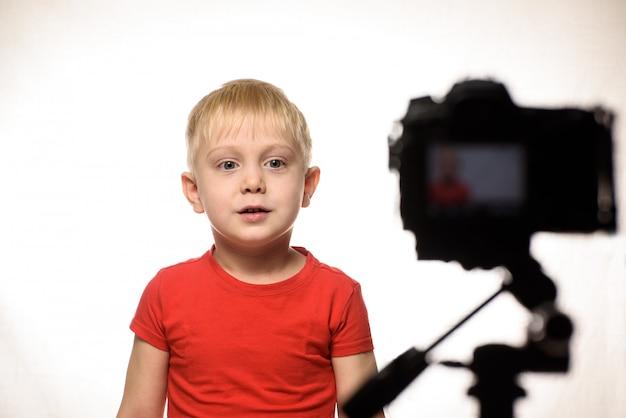 Серьезный белокурый мальчик записывает видео на камеру dslr. маленький видео блоггер. белая стена