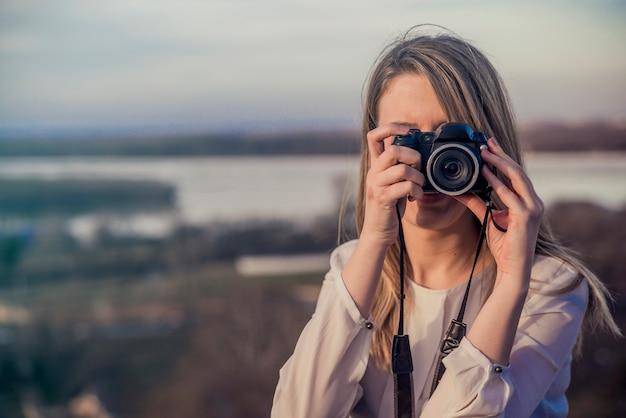 フォトグラファーの女の子は、dslrカメラの写真を撮っています。屋外で写真を撮るためにカメラを使って若い女性を笑って