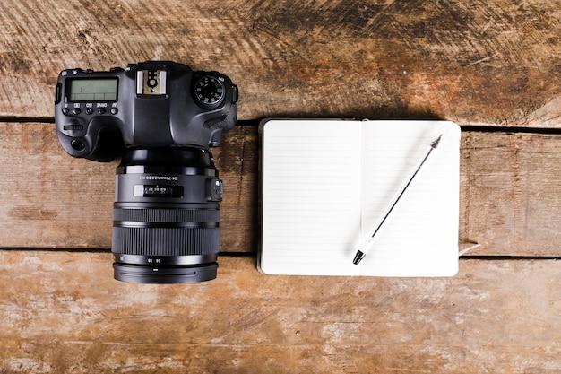 メモ帳のペンとdslrカメラの木製の厚板上の高さのビュー