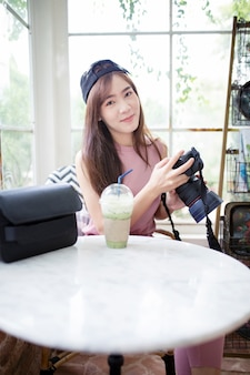 Младшая азиатская женщина, держащая камеру dslr в руке с лицом счастья