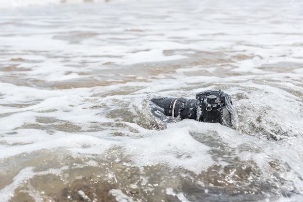 Dslr камера на пляже мокрый от воды морской волны