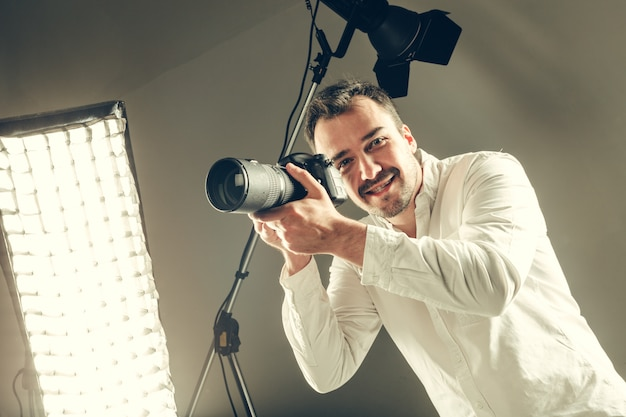 Красивый молодой человек с фотоаппаратом dslr.