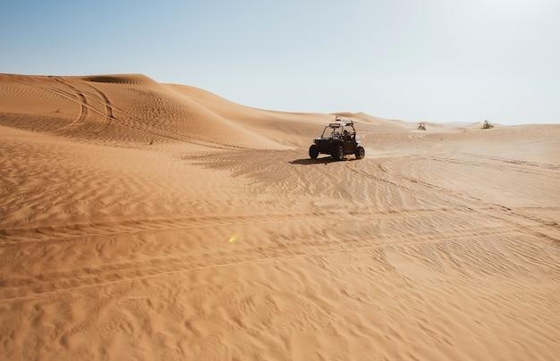 두바이 알 위르 사막에는 바퀴가 있고 더위 속에서 버기 쿼드 바이크를 타고 있습니다.