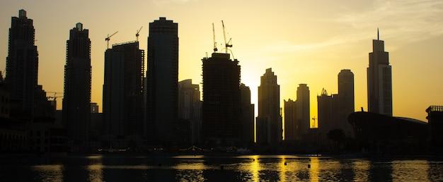 ドバイのビーチと日没時の高層ビル