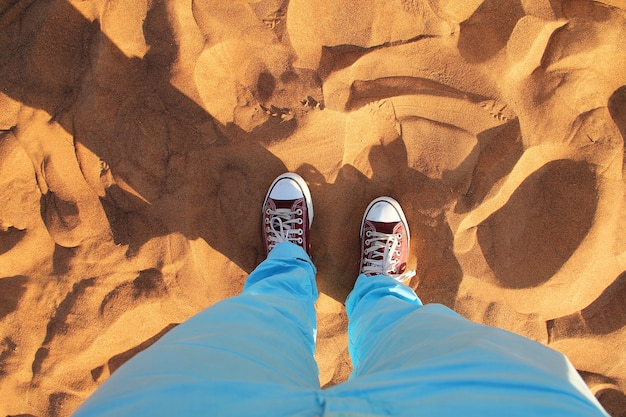 Dubai desert sand close up with read sneakers