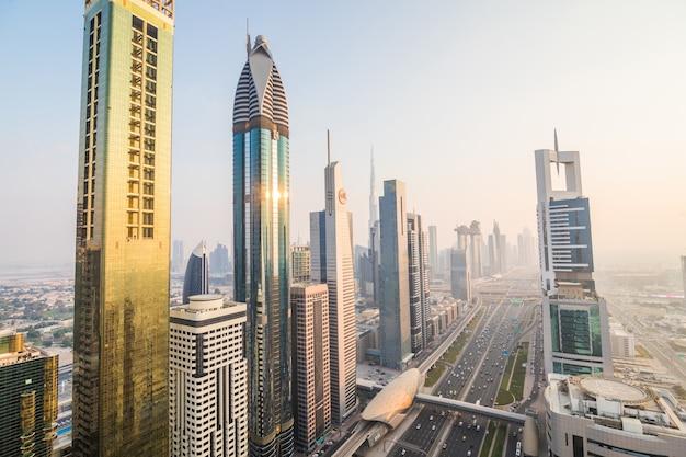두바이 스카이 라인과 일몰에 시내 고층 빌딩. 아랍 에미리트의 세계적으로 유명한 대도시에 고층 건물이있는 현대 건축 개념