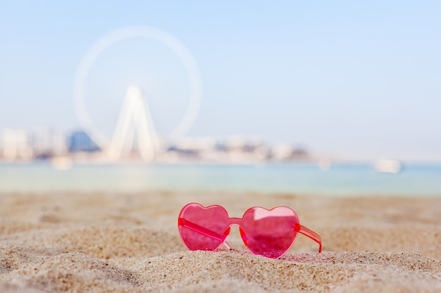 Dubai, uae, november 2019. pink sunglasses on a sandy beach with views of the bluewaters island and the dubai eye ferris wheel, honeymoon, relaxation, copy space