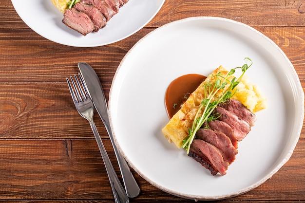 Утиная грудка с гарниром из картофельных запеканок, приправленная гороховым микрогрин с томатно-чили соусом. на белой тарелке. на деревянном фоне