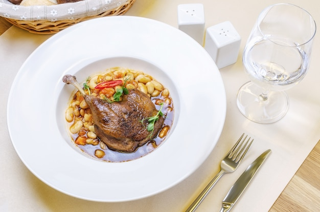 Duck confit leg with white bean garnish