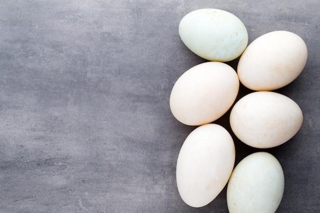 Утиные яйца на сером фоне клетки.