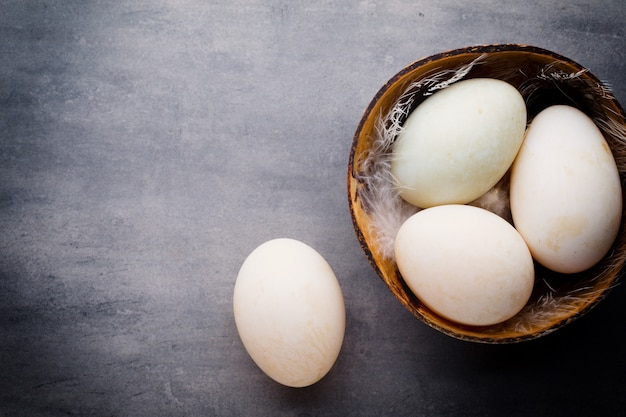 ケージの灰色のテーブルにアヒルの卵。