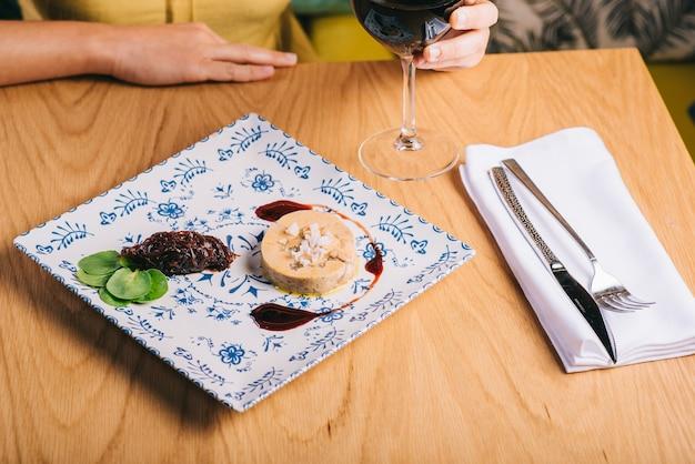 Блюдо из утиной фуа-гра с соусом на деревянном столе и девушка с бокалом вина