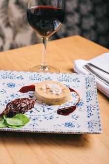 Утиное фуа-гра с соусом на деревянном столе и бокал вина