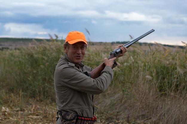 Охотник на уток с ружьем идет по лугу.