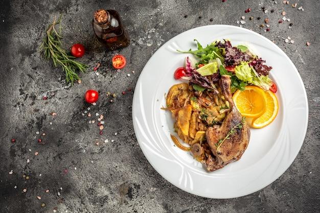 ベイクドポテト、マッシュルーム、玉ねぎを使った鴨のコンフィ肉部分。バナー、メニュー、テキストのレシピの場所、上面図。