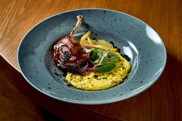 Duck leg confit with polenta and caramelized pear, served in a blue plate on a wooden background.