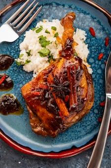 Утиная ножка конфи с рисом и ягодами годжи. традиционная французская кухня. вид сверху.