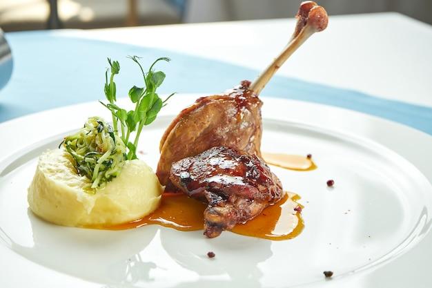 Конфи из утиной ножки в сладком соусе с картофельным пюре в белой тарелке на синей скатерти