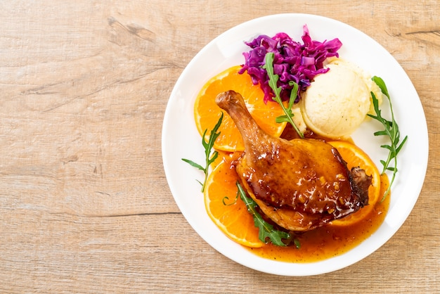 Duck leg steak with orange sauce background