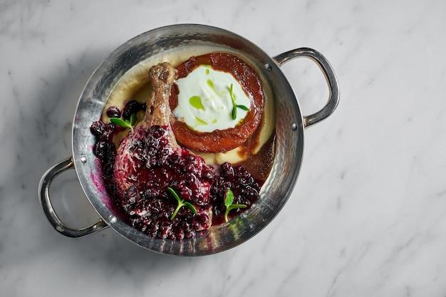 Утиная ножка с клюквенным соусом с гарниром из картофельного пюре и глазированного яблока со сливочным соусом в медном блюде на белом мраморе