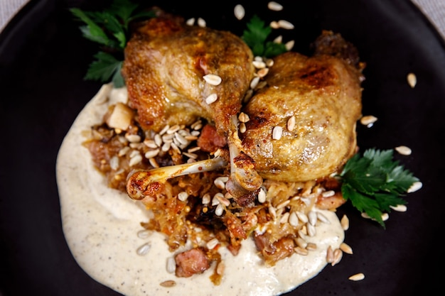 Duck leg with white sauce on a dark plate.