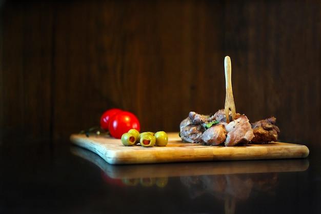 Утиное мясо с помидорами и оливками на деревянной доске изысканная вкусная еда и концепция приготовления