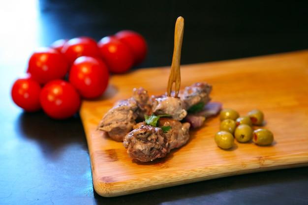 Утиное мясо с помидорами и оливками на деревянной доске деревенская еда, подающая еда и концепция приготовления