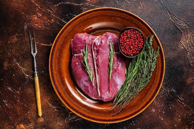 Утиные стейки из сырых грудок на деревенской тарелке с розмарином. вид сверху.