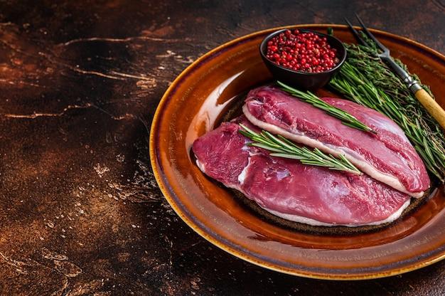 Стейки из утиной грудки на деревенской тарелке с розмарином
