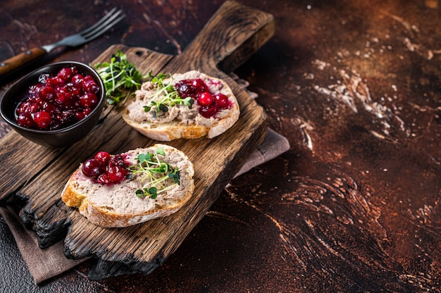 Duck rillettes pate toasts with sprouts on a wooden board.   top view.