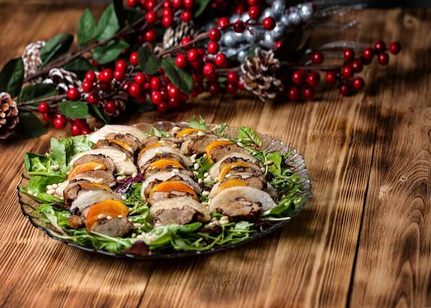 松の実で味付けした木製テーブルに洋ナシの鴨サラダ