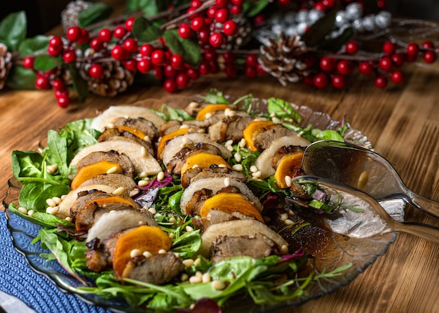 Duck salad with pear on a wooden table, seasoned with pine nuts