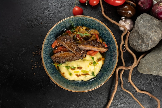 Duck steak with mashed potatoes and vegetables. a hot main course made from poultry, potatoes and stewed vegetables