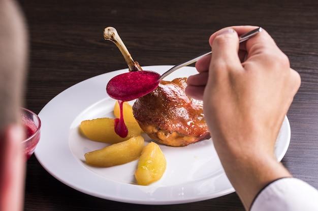 鴨の脚の皿にクランベリーソースのフライドポテトと鴨