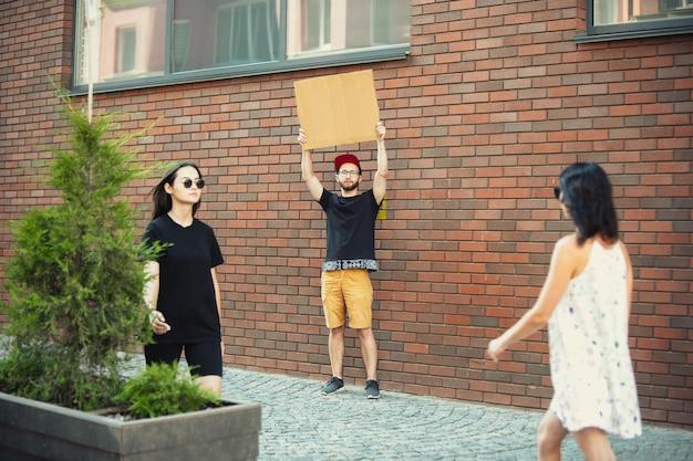 표지판이 있는 친구 - 남자는 그를 짜증나게 하는 것에 항의하는 서 있습니다.