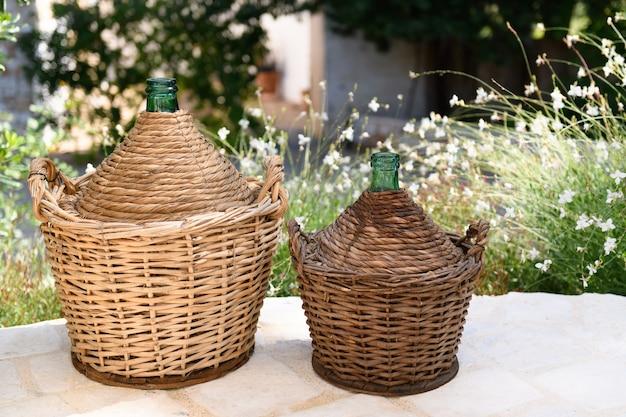プーリアで作られた庭のデミジョンはガラスの容器で、バスケットの形をした籐織りで覆われ、木製の底で覆われ、伝統的なワインの保存方法を入れることができます