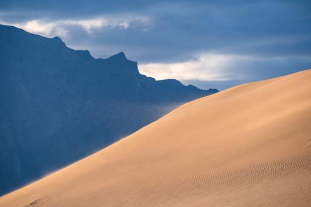 Из-за небольшого ветра песок летит с пустынной возвышенности чарских песков, на заднем плане видна гора с забайкальского хребта.